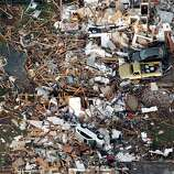 This aerial photo shows the remains of houses in Moore, Okla., following a tornado Monday, May 20, 2013. A tornado roared through the Oklahoma City suburbs Monday, flattening entire neighborhoods, setting buildings on fire and landing a direct blow on an elementary school. (AP Photo/Steve Gooch)