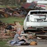 Kay James holds her cat as she sits in her driveway after her home was destroyed by the tornado that hit the area on Monday, May 20, 2013 in Oklahoma City, Okla.