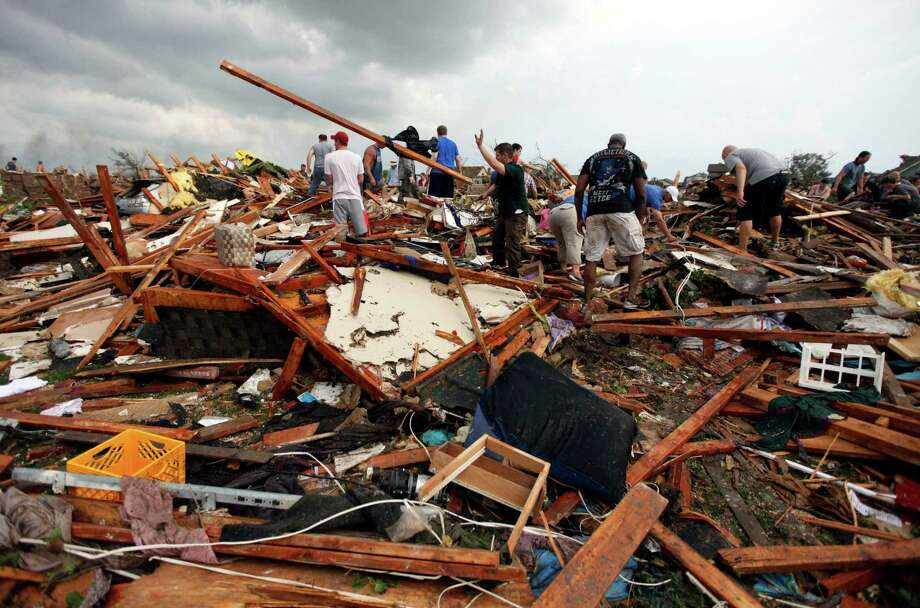 Workers look for victims under debris from a tornado that passed across south Oklahoma City, Monday, May 20, 2013. A monstrous tornado roared through the Oklahoma City suburbs, flattening entire neighborhoods with winds up to 200 mph, setting buildings on fire and landing a direct blow on an elementary school. Photo: The Oklahoman, Paul Hellstern