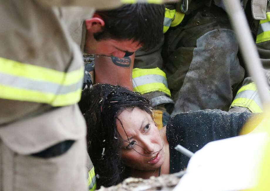 A woman is pulled out from under tornado debris at the Plaza Towers School in Moore, Okla., Monday, May 20, 2013. A tornado as much as half a mile (.8 kilometers) wide with winds up to 200 mph (320 kph) roared through the Oklahoma City suburbs Monday, flattening entire neighborhoods, setting buildings on fire and landing a direct blow on an elementary school. Photo: AP