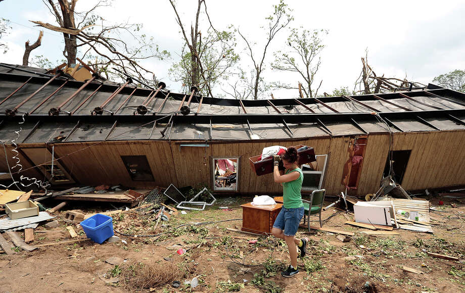 A volunteer helps clean up Jean McAdams' mobile home after it was overturned by a tornado May 20, 2013 near Shawnee, Oklahoma. A series of tornados moved across central Oklahoma May 19, killing two people and injuring at least 21. Photo: Brett Deering, Getty Images / 2013 Getty Images