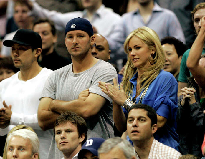 Dallas Cowboys quarterback Tony Romo, left, sits with Candice Crawford during the second half of an