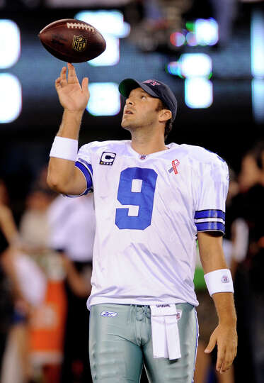 Dallas Cowboys quarterback Tony Romo plays with a football before an NFL football game between the D