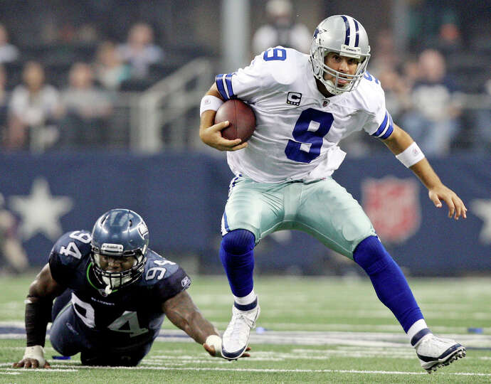 Dallas Cowboys quarterback Tony Romo heads up field around Seattle's Anthony Hargrove during second
