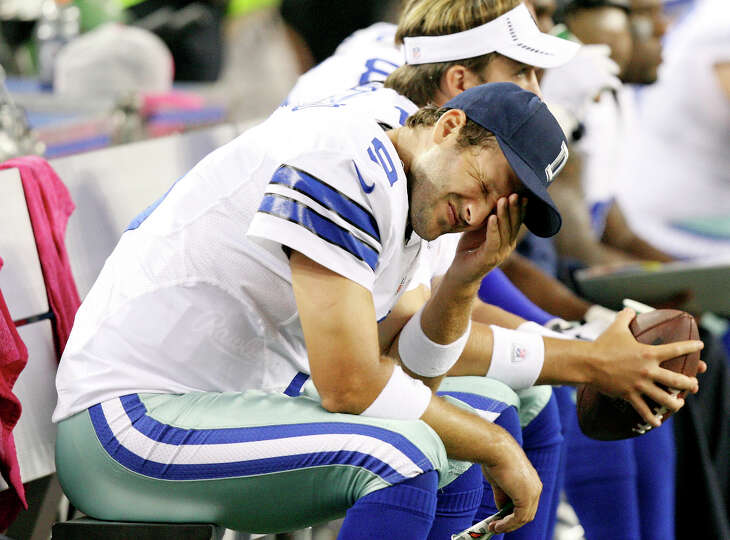 Cowboys quarterback Tony Romo sits dejected on the bench during second half action against the Chica