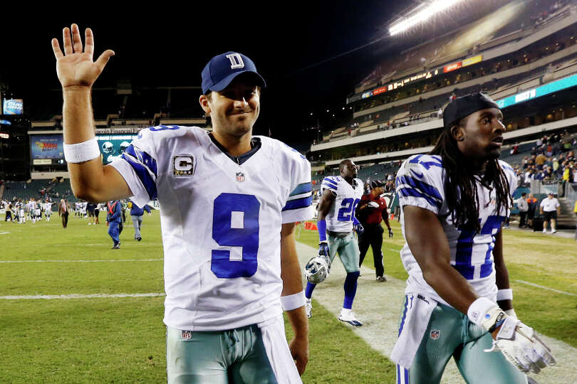 Dallas Cowboys quarterback Tony Romo, left, and wide receiver Dwayne Harris walk off the field after