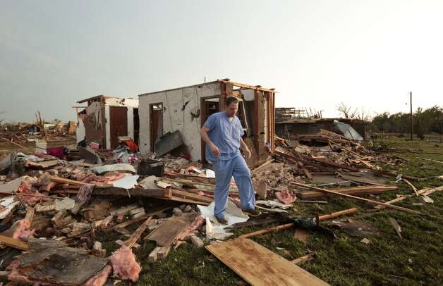MOORE, OK- MAY 20:  Nathan Ulepich searches outside the back of his house destroyed after a powerful tornado ripped through the area on May 20, 2013 in Moore, Oklahoma. The tornado, reported to be at least EF4 strength and two miles wide, touched down in the Oklahoma City area on Monday killing at least 51 people. (Photo by Brett Deering/Getty Images)
