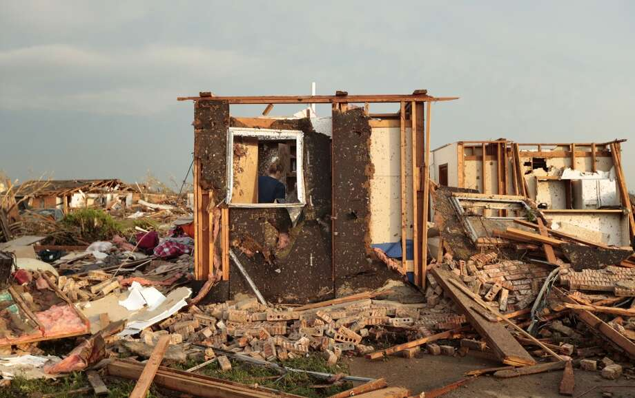 MOORE, OK- MAY 20:  Dana Ulepich searches inside a room left standing at the back of her house destroyed after a powerful tornado ripped through the area on May 20, 2013 in Moore, Oklahoma. The tornado, reported to be at least EF4 strength and two miles wide, touched down in the Oklahoma City area on Monday killing at least 51 people. (Photo by Brett Deering/Getty Images) ***BESTPIX***