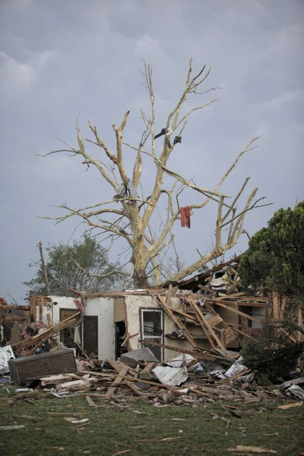 MOORE, OK - MAY 20:  Debris hangs from a tree over a destroyed home after a powerful tornado ripped through the area on May 20, 2013 in Moore, Oklahoma. The tornado, reported to be at least EF4 strength and two miles wide, touched down in the Oklahoma City area on Monday killing at least 51 people. (Photo by Brett Deering/Getty Images)