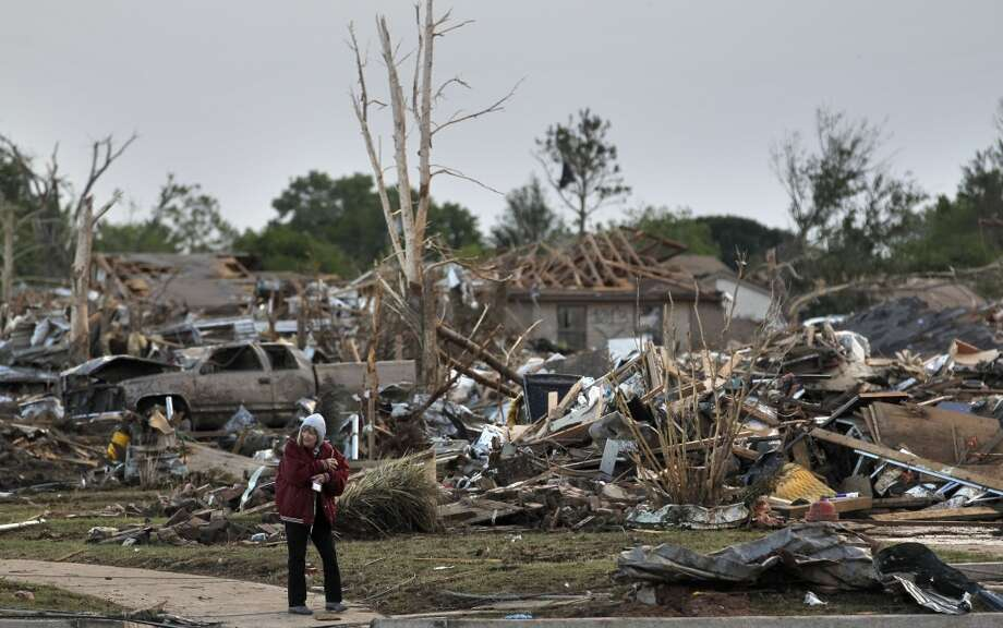 A local resident allowed by security officers into an otherwise sealed off neighborhood walks past the rubble of destroyed homes, one day after a tornado moved through Moore, Okla., Tuesday, May 21, 2013. The huge tornado roared through the Oklahoma City suburb Monday, flattening entire neighborhoods and destroying an elementary school with a direct blow as children and teachers huddled against winds up to 200 mph. (AP Photo/Brennan Linsley)