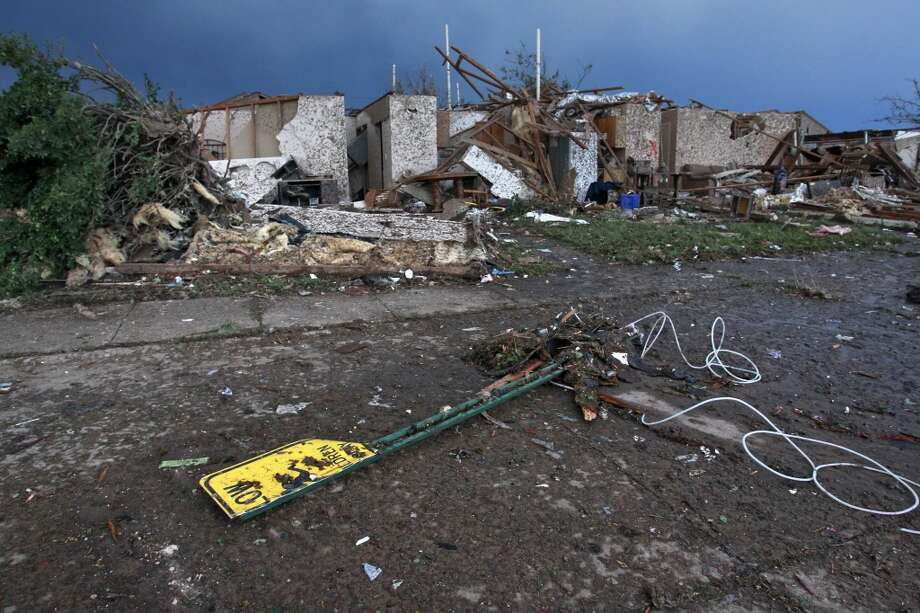 The rubble of a destroyed neighborhood lay where they fell a day earlier Tuesday, May 21, 2013, after a tornado moved through Moore, Okla. The huge tornado roared through the Oklahoma City suburb Monday, flattening entire neighborhoods and destroying an elementary school with a direct blow as children and teachers huddled against winds. (AP Photo/Brennan Linsley)