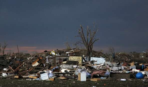 The rubble of a destroyed neighborhood lay mixed together where it fell  Tuesday, May 21, 2013 a day after a tornado moved through Moore, Okla. The huge tornado roared through the Oklahoma City suburb Monday, flattening entire neighborhoods and destroying an elementary school with a direct blow as children and teachers huddled against winds. (AP Photo/Brennan Linsley)