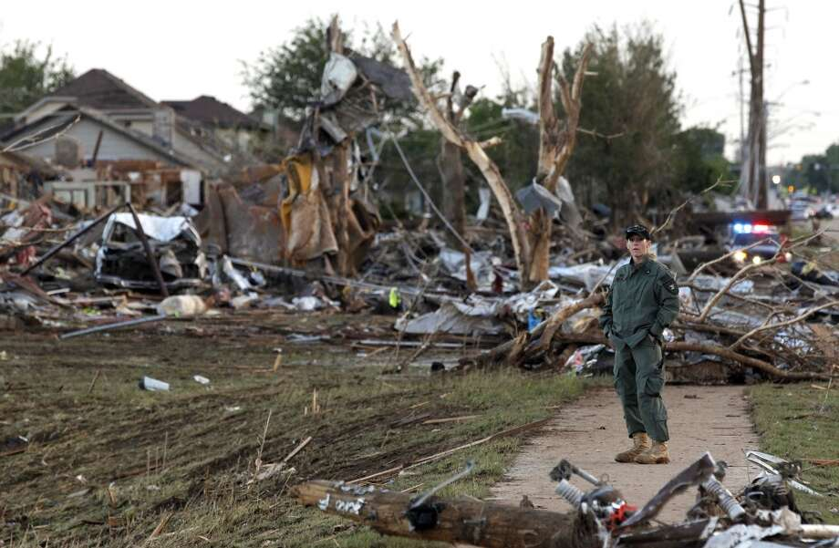 A member of a security team helps guard an area of rubble from a destroyed residential neighborhood, one day after a tornado moved through Moore, Okla., Tuesday, May 21, 2013. The huge tornado roared through the Oklahoma City suburb Monday, flattening entire neighborhoods and destroying an elementary school with a direct blow as children and teachers huddled against the winds. (AP Photo/Brennan Linsley)