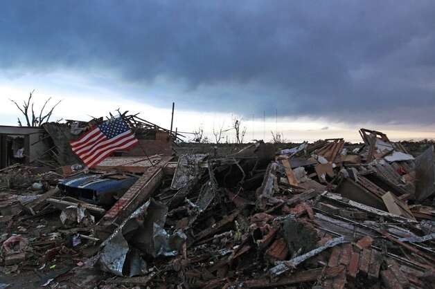 An American flag blows in the wind at sunrise atop the rubble of a destroyed home a day after a tornado moved through Moore, Okla., Tuesday, May 21, 2013. The monstrous tornado roared through the Oklahoma City suburb Monday, flattening entire neighborhoods and destroying an elementary school with a direct blow as children and teachers huddled against winds up to 200 mph. (AP Photo/Brennan Linsley)