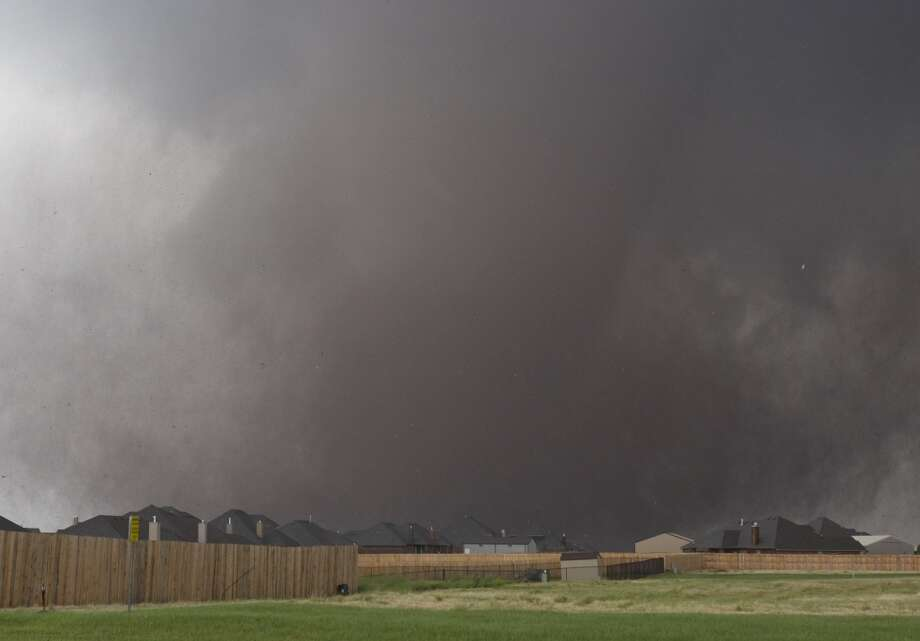 A tornado moves past homes in Moore, Okla. on Monday, May 20, 2013. A monstrous tornado roared through the Oklahoma City suburbs, flattening entire neighborhoods with winds up to 200 mph, setting buildings on fire and landing a direct blow on an elementary school. (AP Photo/Alonzo Adams)