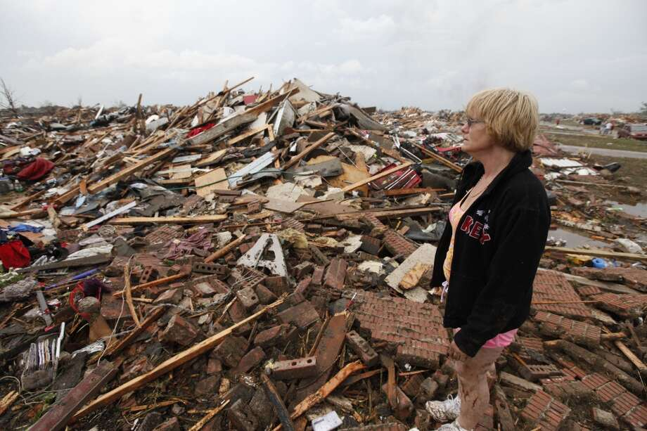 Resident Kim Schwab looks over her destroyed home in south Oklahoma City, Monday, May 20, 2013. A monstrous tornado roared through the Oklahoma City suburbs, flattening entire neighborhoods with winds up to 200 mph, setting buildings on fire and landing a direct blow on an elementary school. (AP Photo/The Oklahoman, Paul Hellstern)