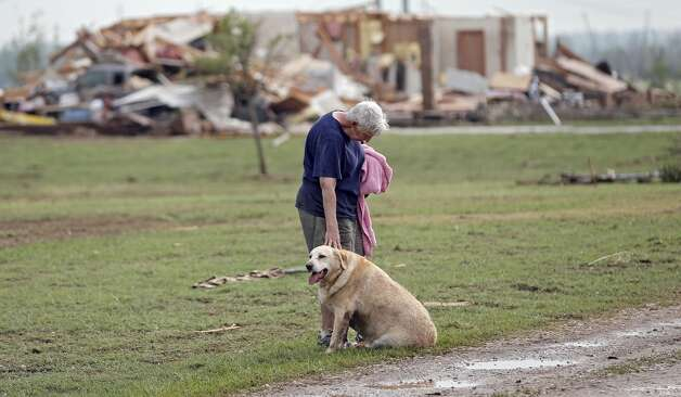 Kay Taylor stands with her dog Bailey in front of her house that was destroyed after the tornado that hit the area near 149th and Drexel on Monday, May 20, 2013 in Oklahoma City, Okla.  (AP Photo/ The Oklahoman, Chris Landsberger)