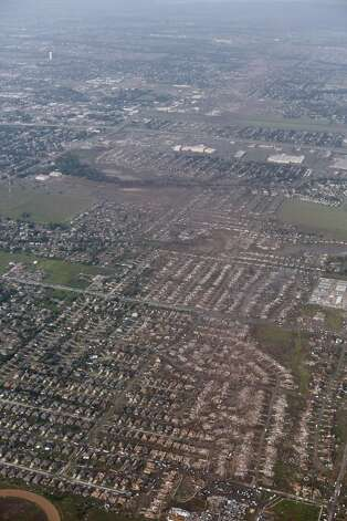 This aerial photo shows the path of a massive tornado in Moore, Okla., Monday May 20, 2013. The tornado roared through the Oklahoma City suburbs Monday, flattening entire neighborhoods, setting buildings on fire and landing a direct blow on an elementary school. (AP Photo/Steve Gooch)