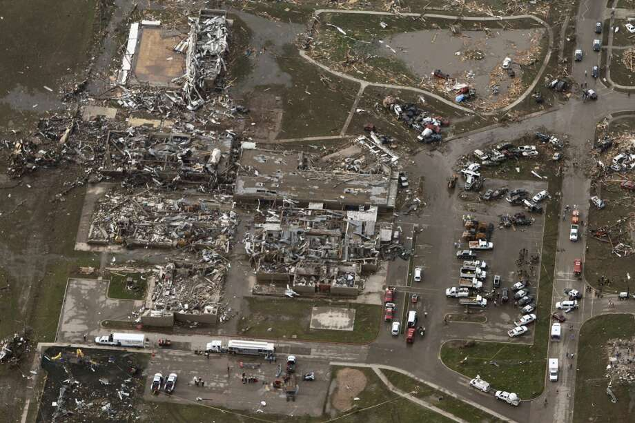 This aerial photo shows damage to buildings hit by a massive tornado in Moore, Okla., Monday May 20, 2013. A tornado roared through the Oklahoma City suburbs Monday, flattening entire neighborhoods, setting buildings on fire and landing a direct blow on an elementary school. (AP Photo/Steve Gooch)