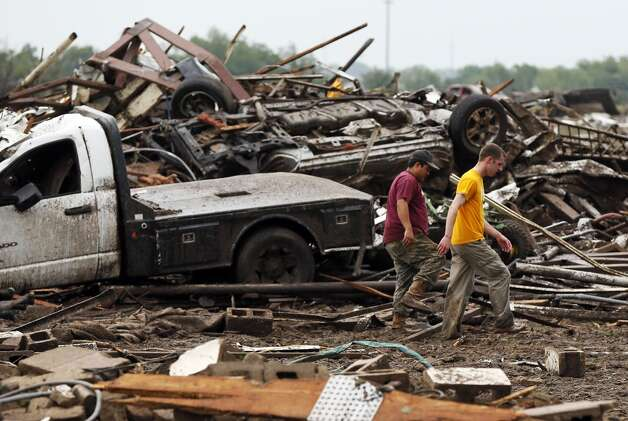 Two men walk through debris just east of Western and north of SW 149th after a tornado struck south Oklahoma City and Moore, Okla., Monday, May 20, 2013. (AP Photo/ The Oklahoman, Nate Billings)
