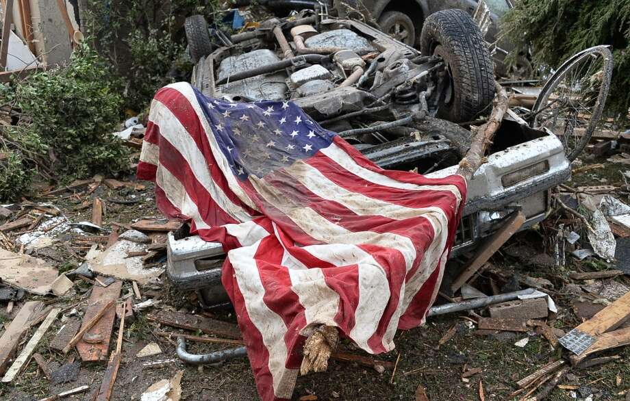 A U.S. flag lays draped across an upturned car in the aftermath of a tornado in Moore, Oklahoma, Monday, May 20, 2013.  At least 51 people were killed, including at least 20 children, and those numbers were expected to climb, officials said Tuesday. (Gene Blevins/Zuma Press/MCT)