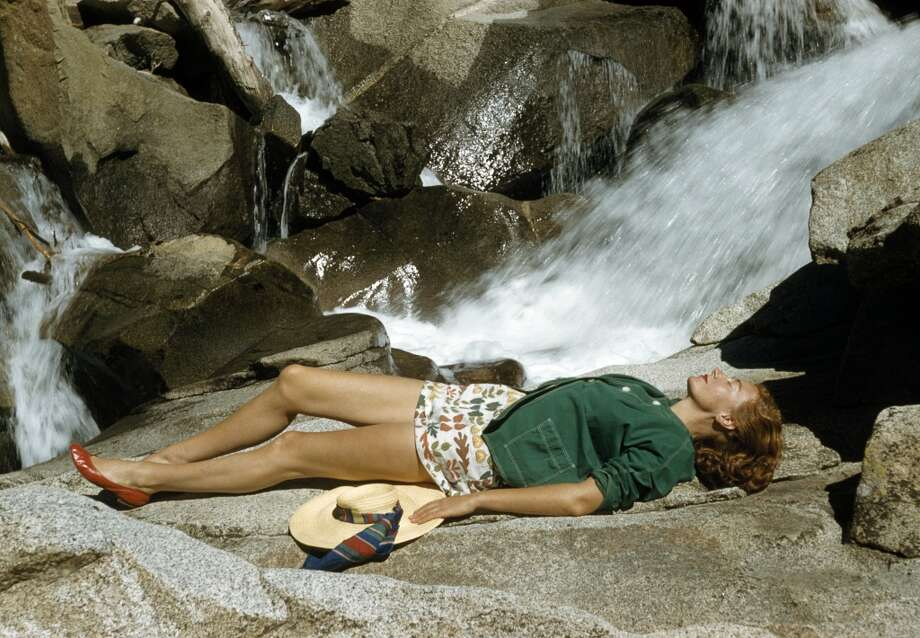 A model with a broad-brimmed straw hat, green denim jacket and a short floral patterned skirt with red shoes sunbathing by a waterfall, circa 1960.  (Photo by Popperfoto/Getty Images)