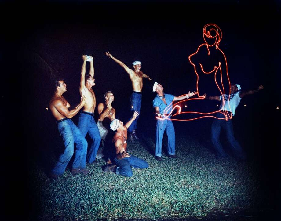 Seven naval officers, four bare-chested, dancing on the beach around a line drawing of a naked woman in red light, in a publicity still issued for the film, South Pacific', 1958. The musical, written by Richard Rodgers (1902–1979) and Oscar Hammerstein II (1895-1960), was directed by Joshua Logan