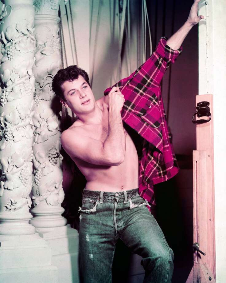 Tony Curtis (1925-2010), US actor, wearing a paid of blue denim jeans, bare-chested as he pulls on a red-and-black plaid shirt, circa 1955.