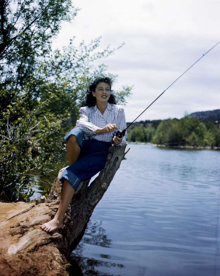 Gail Russell (1924-1961), wearing white blouse with blue stripes, and rolled up denim jeans, holding a fishing rod, circa 1955.