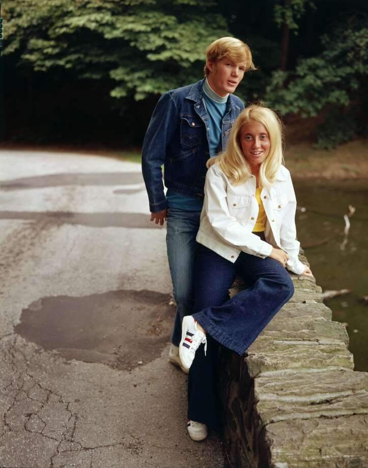 A young man in denim jacket and jeans stands outdoors behind a seated blonde girl in white denim jacket, jeans, and sneakers, circa 1970.