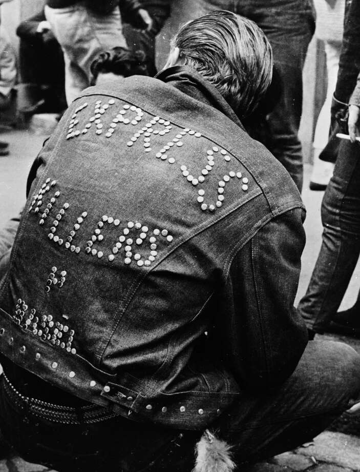 1962:  A man wearing a studded denim jacket bearing the words 'Express Killers' attends a Teddy Boy convention in Zurich.