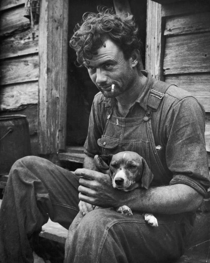 circa 1935:  A tenant farmer in overalls and a denim workshirt holds a beagle on his lap while smoking a cigarette on the steps of a wooden shack in Eastern North Carolina.
