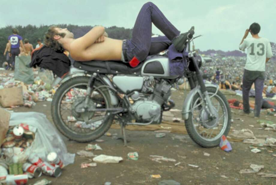 Shirtless man in Levi Strauss jeans lying on motorcycle seat at Woodstock music festival, 1969.