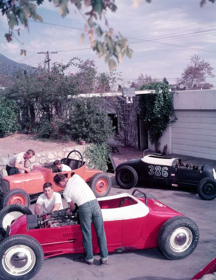 Teenage boys working on a trio of hot rod cars, 1950.