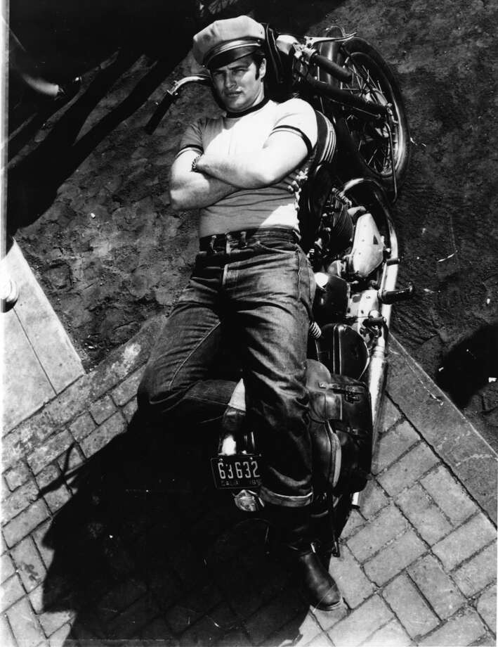 American actor Marlon Brando (1924 - 2004) lies on a motorcycle in a publicity shot for the film 'The Wild One,' directed by Laszlo Benedek, California, 1953.