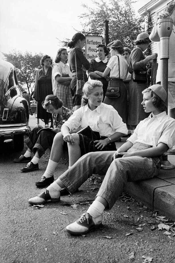 Several Wellesley College students sit on the curb in front of the Hathaway House Bookstore and talk as others stand on the sidewalk behind them, Wellesley, Massachusetts, 1949.