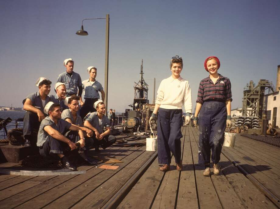 Two female war workers walk along a dock at the Electric Boat Co., cans of paint in their hands, as a group of male sailors watch them Groton, Connecticut, October 1943.