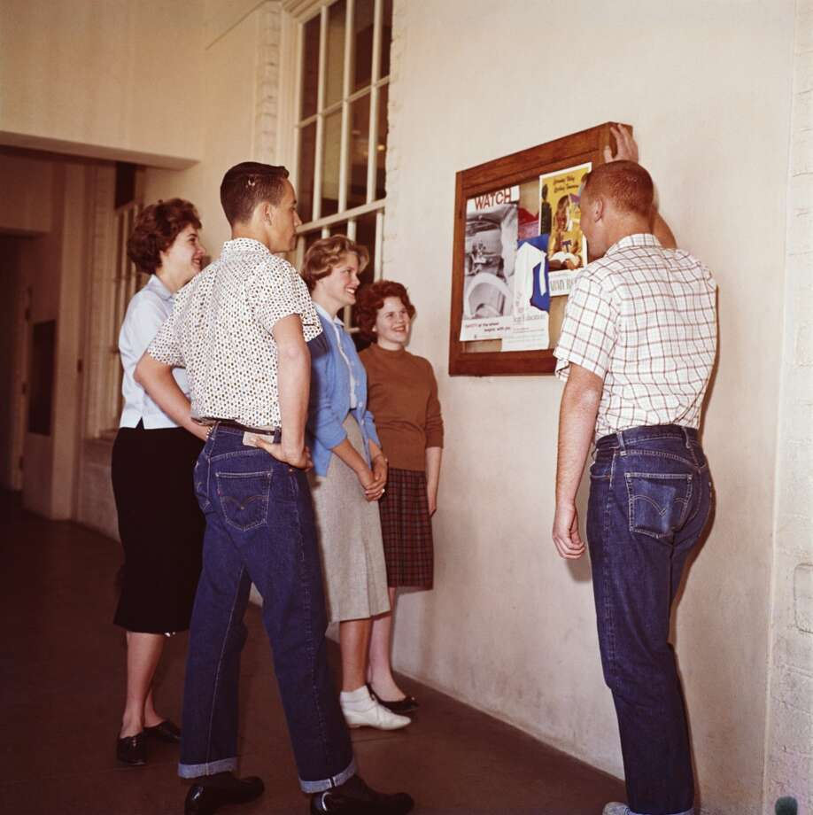 A group of college students looking at a notice board, circa 1960.