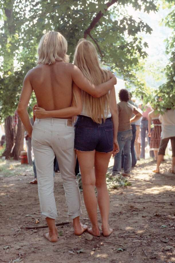 A young blonde couple viewed from behind stand at the back of the crowds at an open air event with their arms around each other circa 1970.