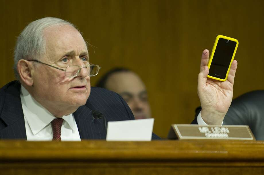 "Chairman of the Permanent Subcommittee on Investigations US Senator  Carl Levin holds up his Apple iPhone as he questions Apple Chief Executive Officer Tim Cook (not seen) about ""offshore profit shifting and the US tax code"" at a hearing on Capitol Hill in Washington, DC, May 21, 2013."