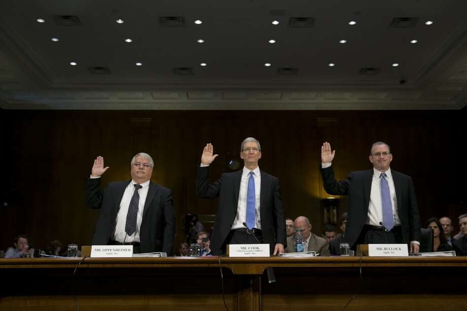 Peter Oppenheimer, senior vice president and chief financial officer of Apple Inc., left to right, Tim Cook, chief executive officer of Apple Inc., and Phillip Bullock, head of tax operations at Apple Inc., swear in to a Senate Permanent Subcommittee on Investigations hearing in Washington, D.C., U.S., on Tuesday, May 21, 2013. Cook will face off against U.S. senators leveling accusations the iPhone maker has created a web of offshore entities to avoid paying billions of dollars in U.S. taxes.