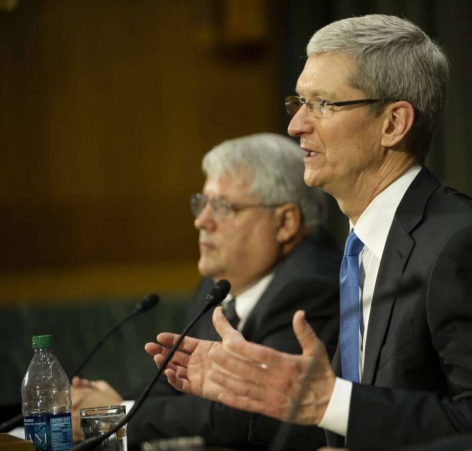 "Apple Chief Executive Officer Tim Cook (R) testifies before the Permanent Subcommittee on Investigations about ""offshore profit shifting and the US tax code"" at a hearing on Capitol Hill in Washington, DC, May 21, 2013, with Chief Financial Officer Peter Oppenheimer (L)."