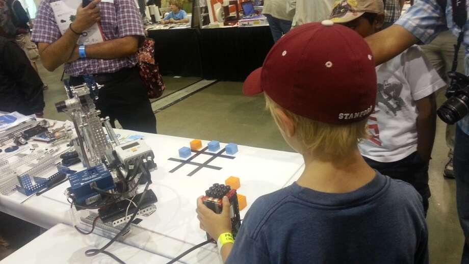 A young maker controls a robot built with LEGO Mindstroms