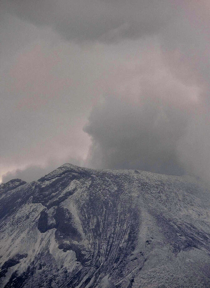 Clouds of ash and smoke are spewed from the Popocatepetl Volcano as seen from Santiago Xalitxintla, in Puebla, Mexico, on May 13, 2013. According to a report by the National Center of Prevention of Disasters (CENAPRED) the yellow alert phase three is still in force. Photo: RONALDO SCHEMIDT, AFP/Getty Images / 2013 AFP