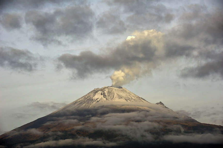 "The Popocatepetl Volcano, Mexico's second highest peak just 55 km southeast of Mexico City, is seen from Santiago Xalitxintla, in Puebla, on May 14, 2013 spewing a cloud of ash and smoke. The National Disaster Prevention Centre (CENAPRED) raised the alert level on Sunday to ""yellow phase three."" Photo: RONALDO SCHEMIDT, AFP/Getty Images / 2013 AFP"