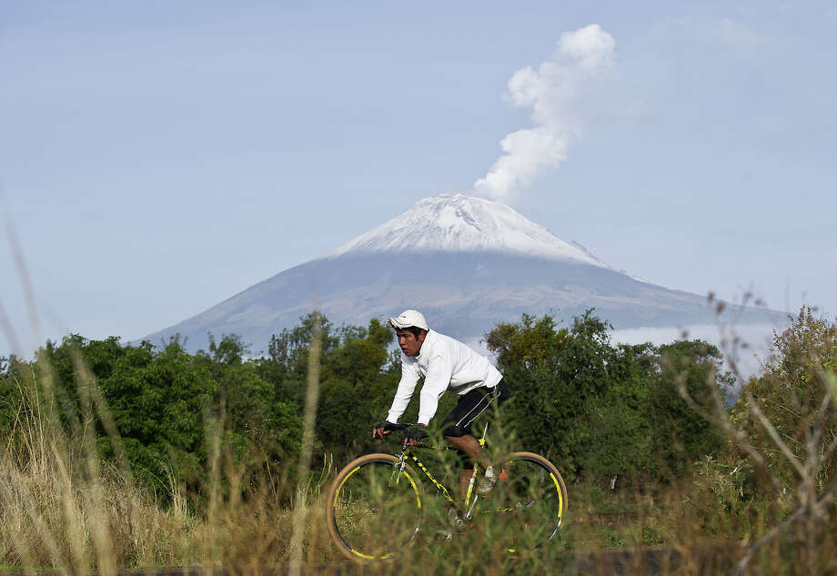 "Backdropped by Popocatepetl Volcano, Mexico's second highest peak just 55 km southeast of Mexico City, a man rides his bicycle in San Nicolas de los Ranchos, in the state of Puebla, on May 14, 2013. The National Disaster Prevention Centre (CENAPRED) raised the alert level on Sunday to ""yellow phase three"" as the Popocatepetl continues to spew ash and smoke. Photo: RONALDO SCHEMIDT, AFP/Getty Images / 2013 AFP"