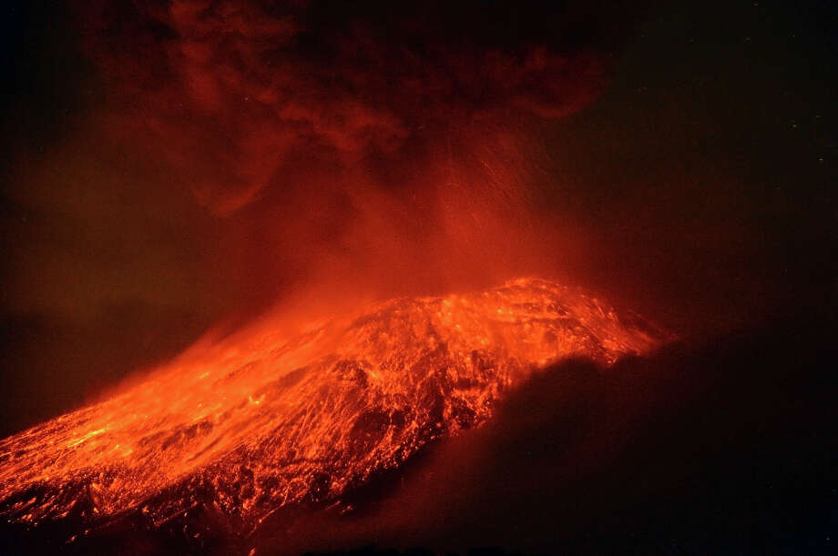 """A cloud of ash belches out of Mexico's Popocatepetl volcano, some 55 km from Mexico City, as seen from Cholula, in the Mexican central state of Puebla, on May 15, 2013. The volcano spewed a new column of ash late Tuesday, with some of the material falling on three towns while glowing rocks landed on the towering mountain's slope. Authorities have raised the alert level to """"Yellow Phase Three,"""" the fifth of a seven-stage warning system, restricting access to an area of 12 km around the volcano while preparing evacuation routes and shelters. Photo: AFP, AFP/Getty Images / 2013 AFP"""