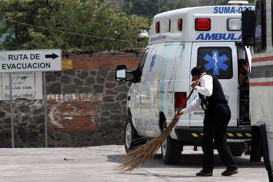 "A man sweeps the street at Santiago Xalitzintla community in Puebla state, near the Popocatepetl Volcano, Mexico's second highest peak, just 55 km southeast of Mexico City, on May 19, 2013. The National Disaster Prevention Centre (CENAPRED) raised the alert level to ""yellow phase three"". The sign reads: ""Evacuation route."" Photo: AFP, AFP/Getty Images / 2013 AFP"