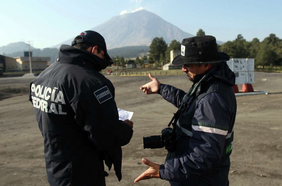 "Two members of the Federal Police talk with the Popocatepetl volcano in the background in Paso de Cortez, at the Popocatepetl-IztaccÌhuatl National Park, Puebla state, 55 km southeast of Mexico City, on May 19, 2013. The National Disaster Prevention Centre (CENAPRED) raised the alert level to ""yellow phase three."" Photo: AFP, AFP/Getty Images / 2013 AFP"