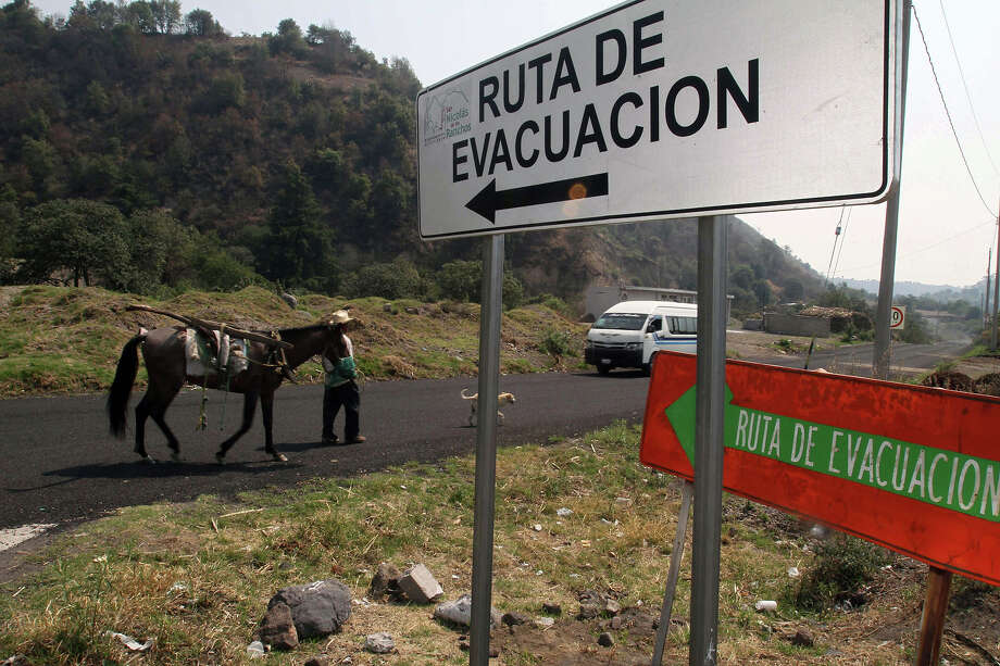 "A man walks with a horse and a dog next to signs reading ""Evacuation route"" in Santiago Xalitzintla community, near the Popocatepetl volcano, Puebla state, 55 km southeast of Mexico City, on May 19, 2013. The National Disaster Prevention Centre (CENAPRED) raised the alert level to ""yellow phase three."" Photo: AFP, AFP/Getty Images / 2013 AFP"